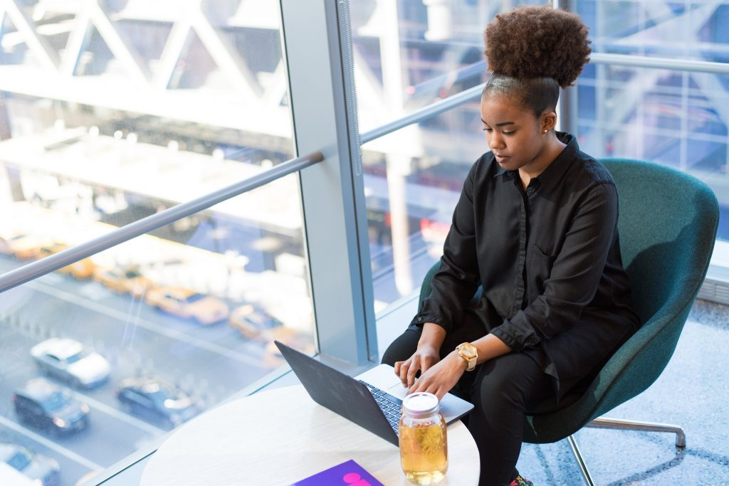 young female employee focuses on work on laptop