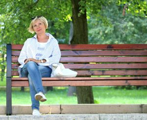 Older lady sits on park bench, deep in thought