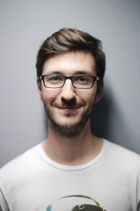 Young male wearing glasses smiles at camera