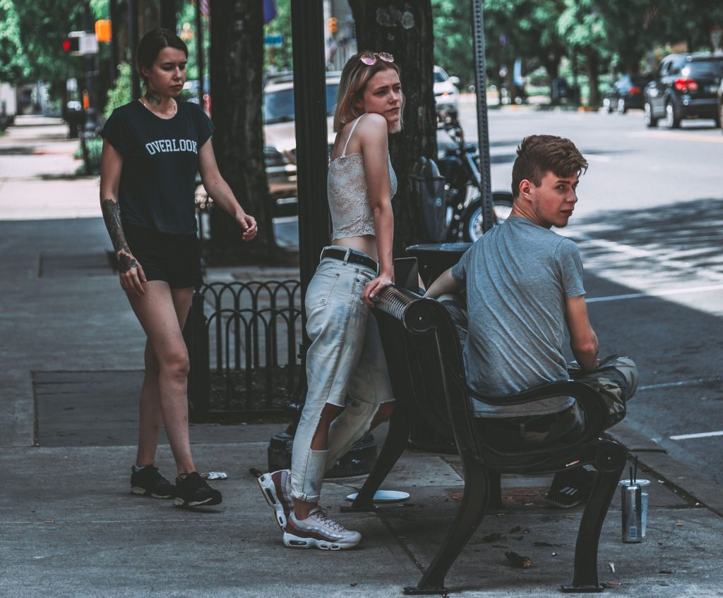 Group of teens loiter around a bench on a street