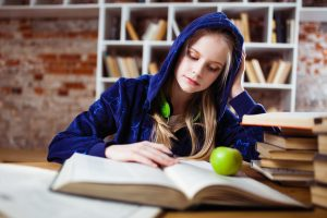 Young female sits at a desk studying a book for her exams