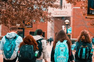 four students walk with backpacks towards university open day