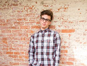 young person standing against wall, casual photo