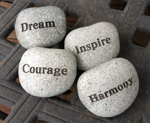 Images of pebbles with dream, courage, inspire and harmony written on them - promoting mental health