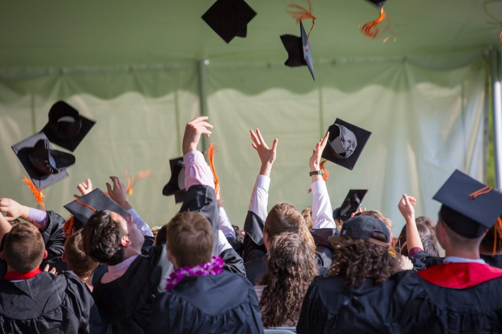 University graduates throwing mortar boards in the air