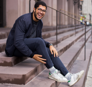 young man sits on steps, laughing