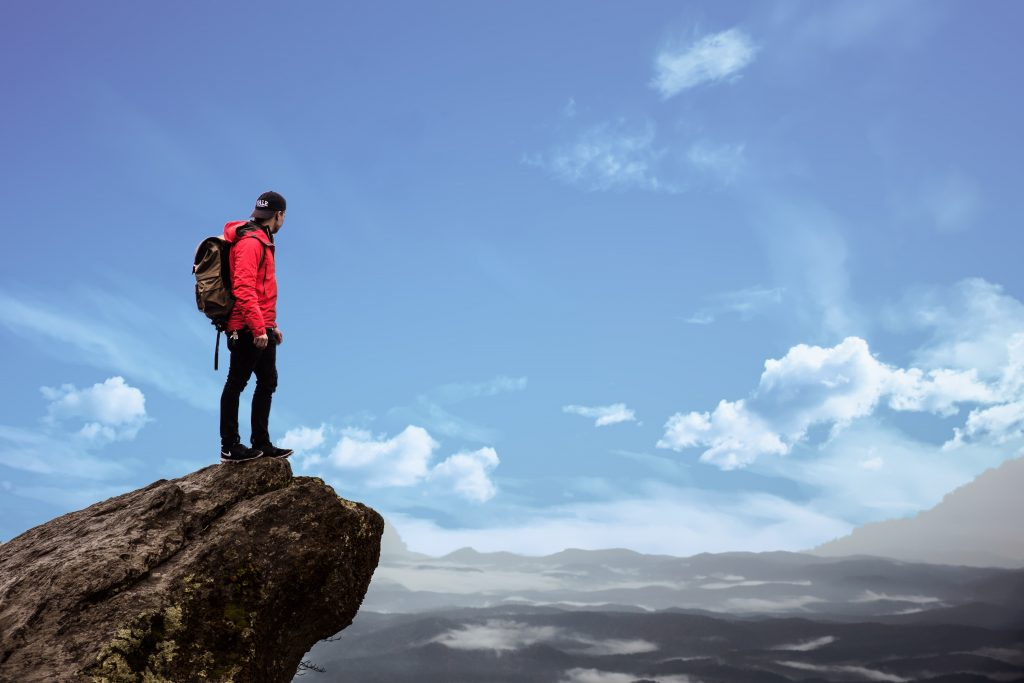 Image of a man standing on a cliff edge